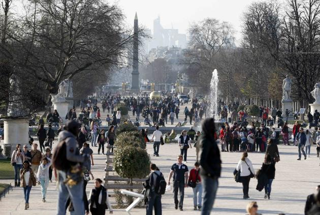 People walk in the Tuileries Garden in central Paris during a warm and sunny winter day