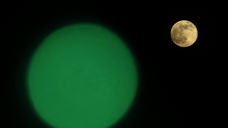 "A Supermoon, right, rises through a clear sky past a green light hanging a boat, in Cairo, Egypt, Sunday, June 23, 2013. The moon, which will reach its full stage on Sunday, is expected to be 13.5 percent closer to earth during a phenomenon known as supermoon. The ""Supermoon"" happens only once this year as the moon on its elliptical orbit is at its closest point to earth. (AP Photo/Hassan Ammar)"