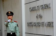"A Chinese paramilitary policeman gestures to photographers at the entrance to the US consulate in Chengdu, Sichuan province, where Wang Lijun sought refuge earlier this year -- kicking off the scandal that brought down high-profile Communist leader Bo Xilai. China has put Wang on ""public"" trial, with the court saying he did not contest the key charges against him"
