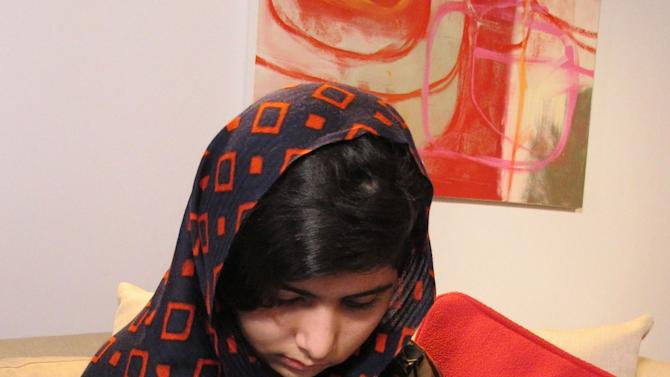 """CORRECTS CREDIT IN CAPTION - In this Jan. 22 2013 photo released  Monday Feb. 4 2013, fifteen-year-old Malala Yousefzai reads get well cards. The Pakistani girl shot by the Taliban on Oct. 9 2012 has made her first video statement since she was nearly killed, released Monday, saying she is recovering. Speaking clearly but with a slight stiffness in her upper lip,  Malala  said that she was """"getting better, day by day."""" (AP Photo/Courtesy of Malala Yousefzai)"""