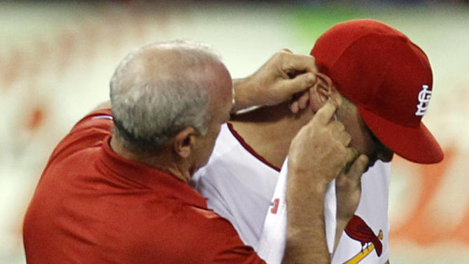 St. Louis Cardinals trainer Barry Weinberg, left, looks at the ear of Cardinals left fielder Matt Holliday during the eighth inning of a baseball game against the Los Angeles Dodgers Monday, Aug. 22, 2011, in St. Louis. Holliday left the game holding his ear. (AP Photo/Jeff Roberson)