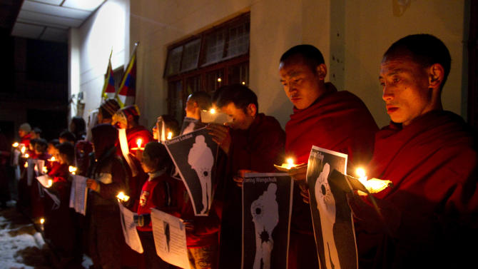 FILE - In this file photo taken Wednesday, Jan. 25, 2012, Tibetan Buddhist monks hold pictures of Tibetans they claim were allegedly shot by Chinese security forces earlier this week, during a candlelight vigil in Dharamsala, India. Three deadly clashes with Chinese security forces in January mark an escalation of a Tibetan protest movement that had expressed itself through scattered individual self-immolations, reflecting both the growing desperation of Tibetans and the harsh response by police. (AP Photo/Angus McDonald, File)