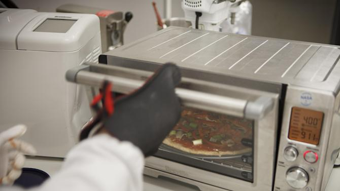Lockheed Martin associate research scientist Monica Leong,  bakes a vegan pizza from a recipe developed for a mission to Mars at NASA's Advanced Food Technology Project at Johnson Space Center in Houston Tuesday, July 3, 2012. NASA is currently planning a mission to Mars, which has gravity, so more options for food preparation, like chopping vegetables, are available as opposed to the dehydrated fare of current space missions. (AP Photo/Michael Stravato)