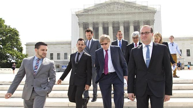 FILE - In this June 20, 2013 file photo, Chad Griffin, right, president of the Human Rights Campaign, leaves the Supreme Court, with Jeff Zarrillo, left, and Paul Katami, second from left, the plaintiffs in the California Proposition 8 case, and their attorney Ted Olson, center, in Washington. Proposition 8 is the California measure that banned same sex marriages. The U.S. Supreme Court is expected to issue a ruling that will determine the fate of California's voter-approved ban on same-sex marriages on Wednesday morning, June 26, 2013. (AP Photo/J. Scott Applewhite, File)