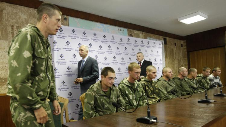 A group of Russian servicemen, who are detained by Ukrainian authorities, arrive at a news conference in Kiev