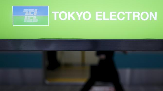 A man walks behind a signboard with logo of Tokyo Electron Ltd in Tokyo
