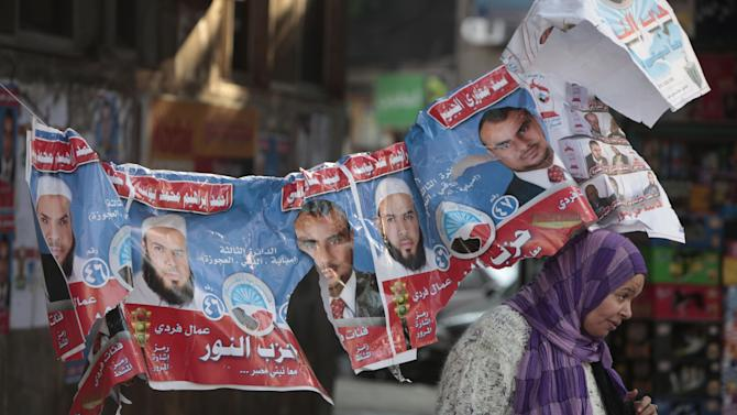 """FILE - In this Monday, Dec. 12, 2011 file photo, An Egyptian woman walks under electoral posters with pictures of candidates of the Salafi Al-Nour party and Arabic that reads, """"Said Maghawri, and Ahmed Ibrahim,"""" in Cairo, Egypt. Egypt's largest ultraconservative Islamist party, which has emerged as a potent political force in the country, elected a new leader on Wednesday after the previous head with dozens of other members broke away to form their own political group following months of infighting. (AP Photo/Amr Nabil, File)"""