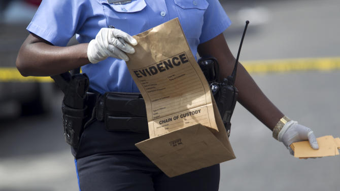 New Orleans police officer collects evidence at the scene of a shooting at the intersection Frenchman Street at N. Villere on Mother's Day in New Orleans, Sunday May 12, 2013. Gunmen opened fire on dozens of people marching in a Mother's Day neighborhood parade in New Orleans on Sunday, wounding at least 17, police said. (AP Photo/Doug Parker)
