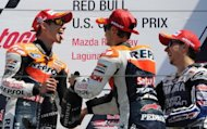 Repsol Honda Team rider Casey Stoner (L) of Australia, Yamaha Factory Racing team rider Jorge Lorenzo (R) of Spain and Repsol Honda team rider Dani Pedrosa of Spain celebrate with champagne after the Red Bull U.S. Moto GP race at Mazda Raceway Laguna Seca in Monterey, California, July 29 2012. Stoner finished first followed by Lorenzo and Pedrosa. AFP PHOTO / ROBYN BECK (AFP | robyn beck)