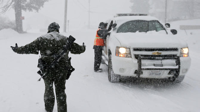 FILE - In this Feb. 8, 2013 file photo, San Bernardino Sheriff's Department offices stand guard at a check point during the search for fired Los Angeles Police Department officer Christopher Dorner in Big Bear Lake, Calif. (AP Photo/Chris Carlson, File)