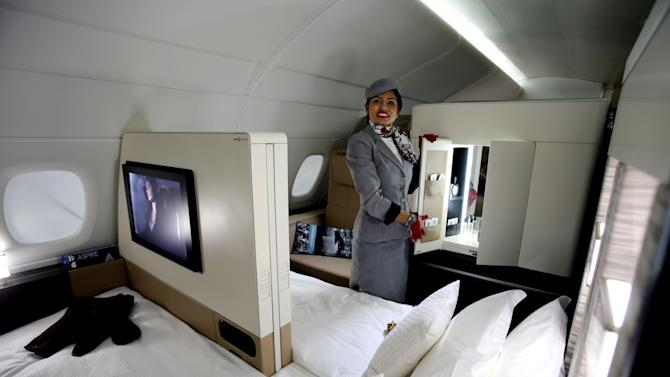 An Etihad Airways official stands inside a mock-up first class cabin, at a training facility in Abu Dhabi, United Arab Emirates, Sunday, May 4, 2014. Etihad Airways, a fast-growing Mideast carrier, laid out plans Sunday to offer passengers who find first-class seats a bit too tight a miniature suite featuring a closed-off bedroom, private bathroom and a dedicated butler. (AP Photo/Kamran Jebreili)