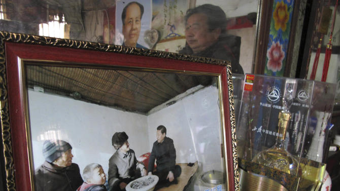 In this photo taken Monday Feb. 25, 2013, a framed state media photograph of new Chinese leader Xi Jinping's visit to corn farmer Tang Rongbin is displayed in Tang's home in Luotuowan village in northern China's Hebei province. Village chief Gu Runjin is seen in the reflection of the mirror behind the photograph. Xi visited Tang in December 2012 as part of efforts to style himself as a no-frills man-of-the-people. Xi has also presented himself as an economic reformer and an iron-fisted graft-buster, spurring expectations for change, but as he prepares to be appointed president, pressure will be growing on him to deliver. (AP Photo/Gillian Wong)