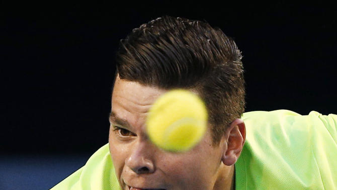 Milos Raonic of Canada stretches to hit a return against Novak Djokovic of Serbia during their men's singles quarter-final match at the Australian Open 2015 tennis tournament in Melbourne