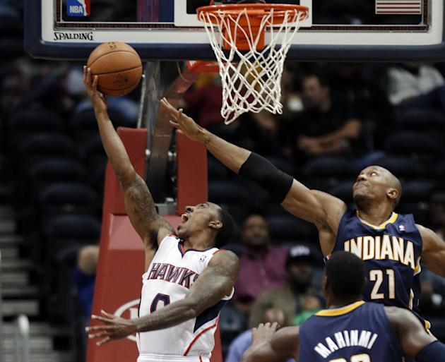 Atlanta Hawks point guard Jeff Teague (0) goes up for a basket as Indiana Pacers power forward David West (21) defends during the first half of a preseason NBA basketball game Tuesday, Oct. 22, 2013,