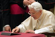 Pope Benedict XVI clicks on a tablet to send his first twitter message during his weekly general audience on December 12, 2012 at the Paul VI hall at the Vatican. The account, which has more than two million followers in nine languages, will close next week when Benedict XVI leaves office