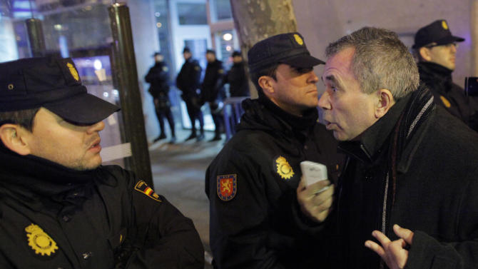 Police stop people as they closed the Popular Party's headquarters area during a protest against corruption in central Madrid, Friday, Jan. 18, 2013. A former Spanish ruling party treasurer amassed 22 million euro ($29 million) in Swiss bank accounts, a court said, prompting a barrage of questions Friday about whether senior officials may have been involved in alleged corruption before taking power in 2011. (AP Photo/Andres Kudacki)
