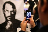 A man uses an iPhone to photograph a painting of the late Apple co-founder Steve Jobs. Some analysts thought Apple might bring in a celebrity to infuse the Wednesday media event with magical energy that has been missing in the absence of Jobs, who died last year