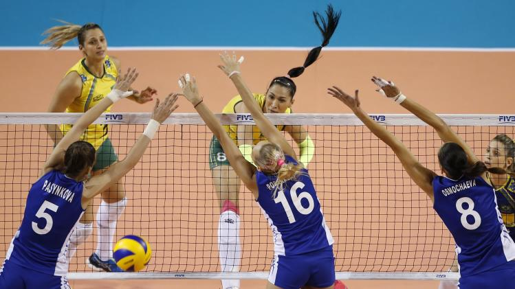 Carvalho of Brazil spikes the ball against Goncharova, Podskalnaya, and Pasynkova of Russia during their FIVB Women's Volleyball World Grand Prix 2014 final round match in Tokyo
