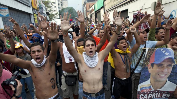Demonstrators, one holding a poster of opposition presidential candidate Henrique Capriles, shout slogans against the government and the official election results in the Altamira neighborhood in Caracas, Venezuela, Monday, April 15, 2013. National Guard troops fired tear gas and plastic bullets to disperse demonstrators protesting the official results in Venezuela's disputed presidential election.(AP Photo/Ramon Espinosa)
