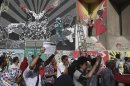 Protesters chant anti-Mursi and anti-Muslim Brotherhood slogans near graffiti during a demonstration in a street leading to Tahrir square, in Cairo
