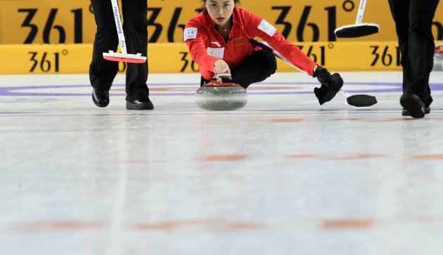 China's second Qinghuang Yue delivers a stone during their World Women's Curling Championship qualification round match against Sweden in Riga