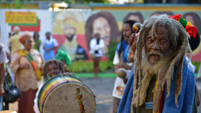 A Rastafarian priest leads a chant during the celebration of reggae music icon Bob Marley's 68th birthday in the yard of his Kingston home, in Jamaica, Wednesday, Feb. 6, 2013. Marley's relatives and old friends were joined by hundreds of tourists to dance and chant to the pounding of drums to honor the late reggae icon who died of cancer in 1981 at age 36. (AP Photo/ David McFadden)