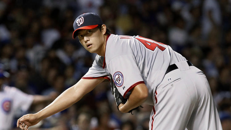 Washington Nationals starting pitcher Chien-Ming Wang checks the runner, Chicago Cubs' Carlos Pena, at first during the fourth inning of a baseball game Tuesday, Aug. 9, 2011, in Chicago. (AP Photo/Charles Rex Arbogast)