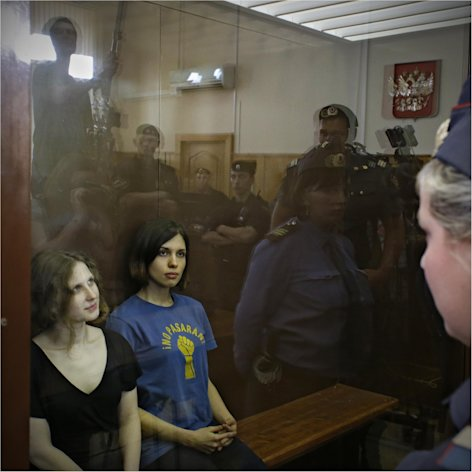 Feminist punk group Pussy Riot members, from left, Maria Alekhina and Nadezhda Tolokonnikova sit in a glass cage at a court room in Moscow, Russia on Friday, Aug. 17, 2012. A judge found three members of the provocative punk band Pussy Riot guilty of hooliganism on Friday, in a case that has drawn widespread international condemnation as an emblem of Russia&#39;s intolerance of dissent. T-shirt on right worn by Tolokonnikova is Spanish and translates to &quot;They shall not pass&quot;, a slogan often used to express determination to defend a position against an enemy. (AP Photo/Sergey Ponomarev)