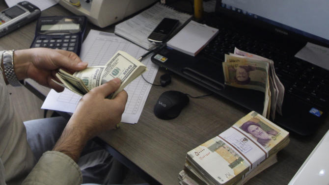 """FILE - A currency exchange bureau worker counts US dollars, as Iranian bank notes are seen at right with portrait of late revolutionary founder Ayatollah Khomeini, in downtown Tehran, Iran, in this Wednesday, Dec. 21, 2011 file photo. The SWIFT financial transaction service says it's cutting ties with Iranian banks that are subject to European sanctions.  In a statement Thursday, March 14, 2012, SWIFT,  the banking hub crucial to oil, financial transactions and other trade, said the EU decision """"prohibits companies such as SWIFT to continue to provide specialized financial messaging services to EU-sanctioned banks,"""" and the company was forced to act.    (AP Photo/Vahid Salemi, File)"""