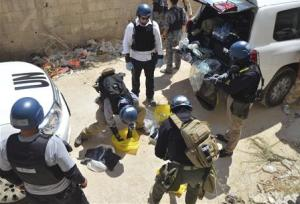 U.N. chemical weapons experts prepare before collecting samples from one of the sites of an alleged chemical weapons attack in Zamalka