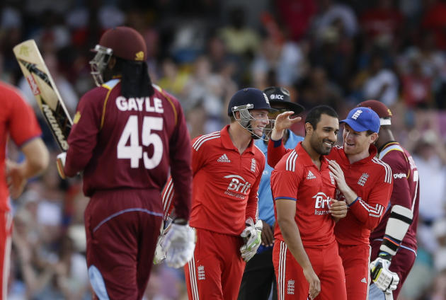 England's Ravi Bopara, second from right, is greeted by England's Eoin Morgan. right, and Jos Buttler after he bowled West Indies' Chris Gayle , left,  during their second T20 Internationa