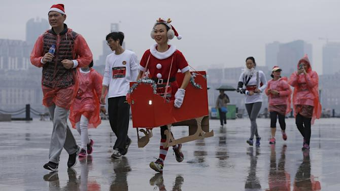 Runners dressed in Christmas-themed outfits compete during a charity Santa run in Shanghai