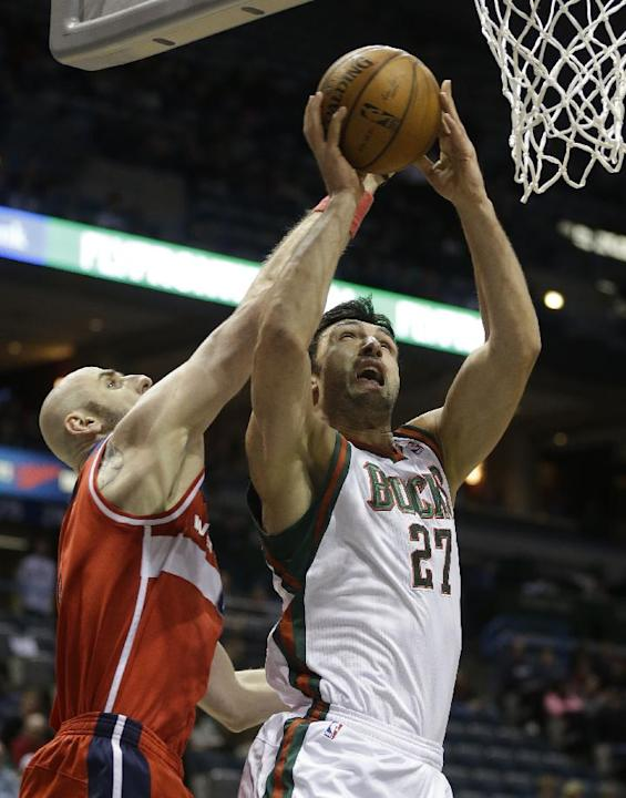 Milwaukee Bucks' Zaza Pachulia (27) shoots against Washington Wizards' Marcin Gortat during the first half of an NBA basketball game on Saturday, March 8, 2014, in Milwaukee
