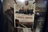 "A poster for the Oscar-nominated documentary ""5 Broken Cameras"" is displayed at a theatre in the West Bank city of Ramallah January 28, 2013. REUTERS/Mohamad Torokman/Files"