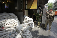 A foreign tourist takes pictures of the entrance of a cafe, fortified with sandbags to stop floodwaters, in Bangkok, Thailand, Friday, Nov. 11, 2011. Thailand is once again in tourist turmoil as floods linger, but ever resilient industry unfazed. (AP Photo/Altaf Qadri)