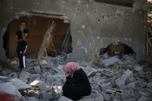 A Palestinian woman reacts upon seeing her destroyed …