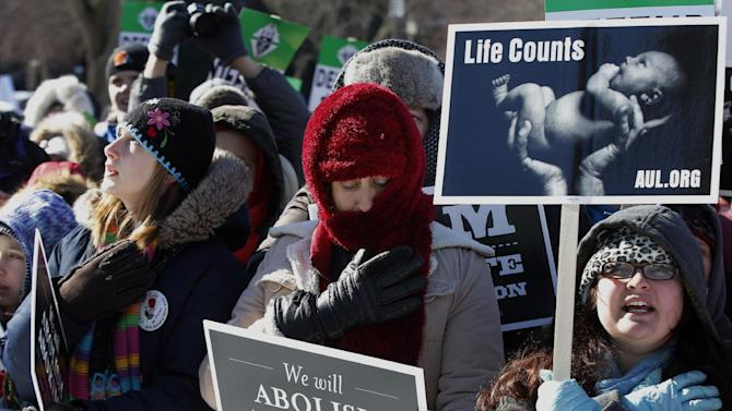 Anti-abortion demonstrators put their hands to their hearts as they recite the Pledge of Allegiance as they rally at the annual March for Life, Wednesday, Jan. 22, 2014, on the National Mall in Washington. Thousands of anti-abortion demonstrators are gathering in Washington for an annual march to protest the Supreme Court's landmark 1973 decision that declared a constitutional right to abortion. (AP Photo/Charles Dharapak)