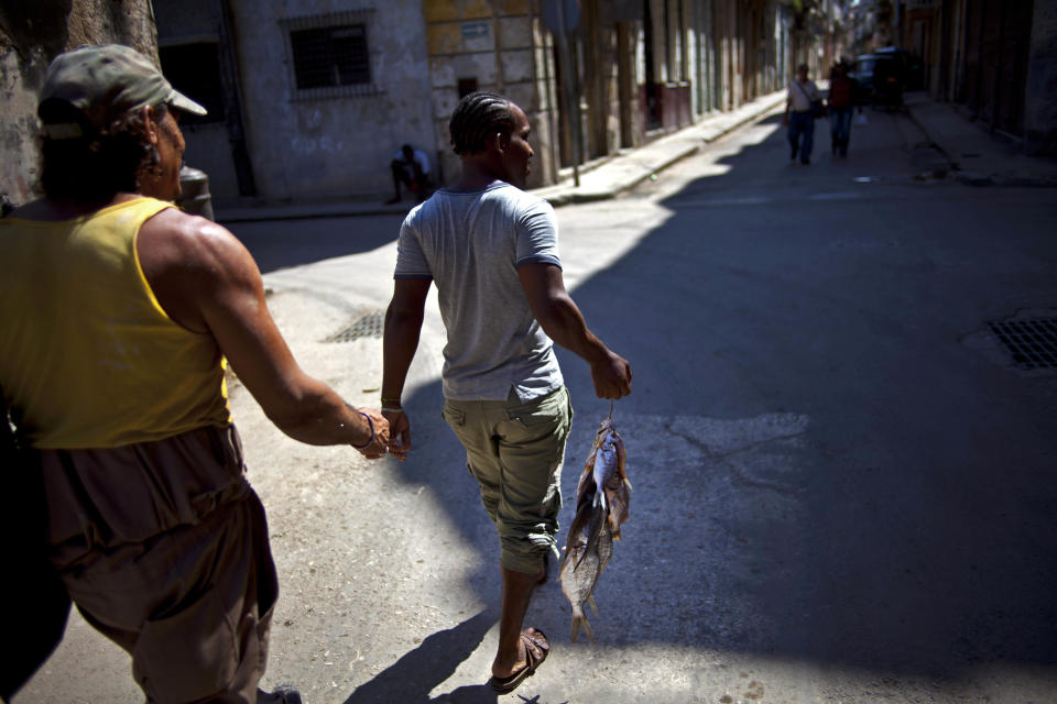 A man carries freshly caught fish to sell in Old Havana, Cuba, Saturday, Oct. 20, 2012.  On Sunday, Cubans will cast ballots to choose among candidates for municipal assemblies that administer local governments and relay complaints on issues such as potholes and housing, social and sports programs. (AP Photo/Ramon Espinosa)