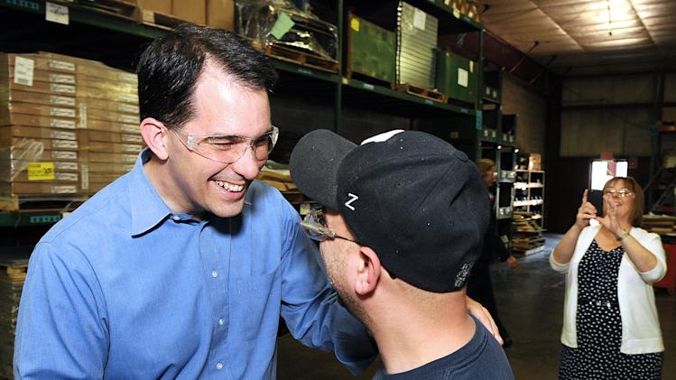 Wisconsin Gov. Scott Walker, left, shakes hands with J & D Manufacturing employee Steve Poppe of Eau Claire, Wis., during a visit Monday, June 4, 2012, to the Altoona, Wis., company. The governor scheduled campaign stops at six of the state's largest cities on the day before Wisconsin's historic recall election. Walker's wife, Tonette, takes a photo, at right.  (AP Photo/The Eau Claire Leader-Telegram,  Steve Kinderman)