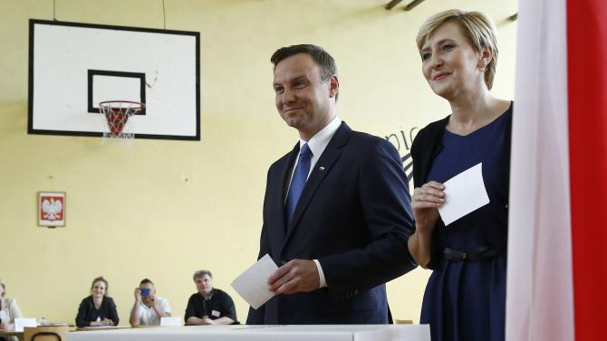 Duda, presidential candidate of the Law and Justice Party (PiS), walks to a ballot box to cast his vote next to his wife Agata in a polling station in Krakow