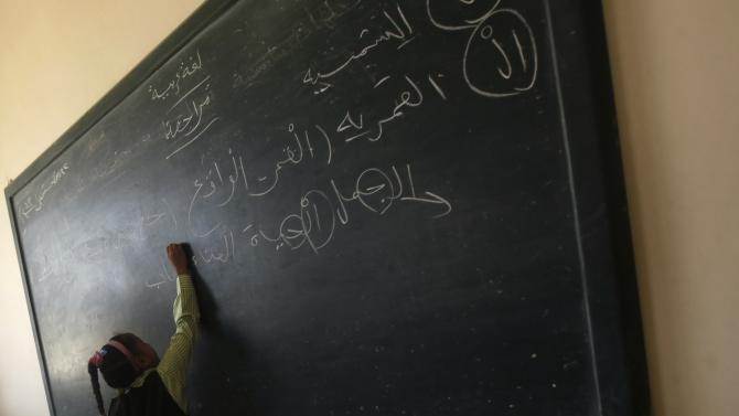 A girl writes on the blackboard on the first day of her new school year at a government school in Giza