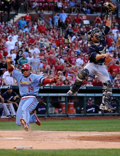 Jon Jay #19 of the St. Louis Cardinals scores on a triple by Daniel Descalso #33 as Jonathan Lucroy #20 of the Milwaukee Brewers leaps for the ball at Busch Stadium on August 5, 2012 in St. Louis, Missouri. (Photo by Jeff Curry/Getty Images)