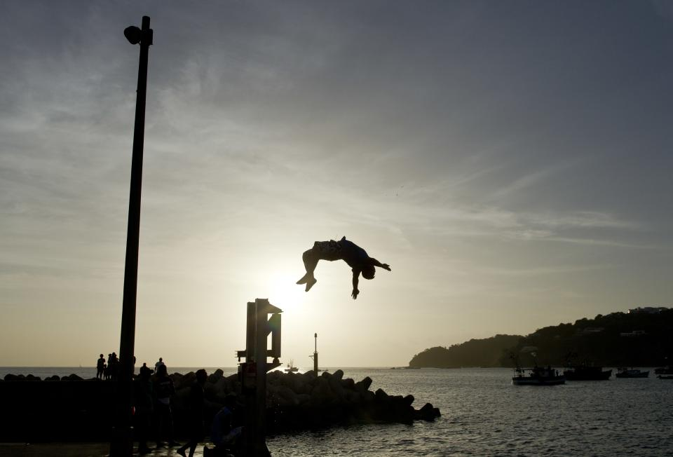A youth jumps into the Pacific Ocean during a religious procession of the Virgin of Carmen on the shores of San Juan del Sur, Nicaragua, Tuesday, July 16, 2013. Nicaragua's fishing community celebrate the feast day of the Virgin Carmen who is worshipped by Catholics as the patron saint of fishermen and sailors. (AP Photo/Esteban Felix)