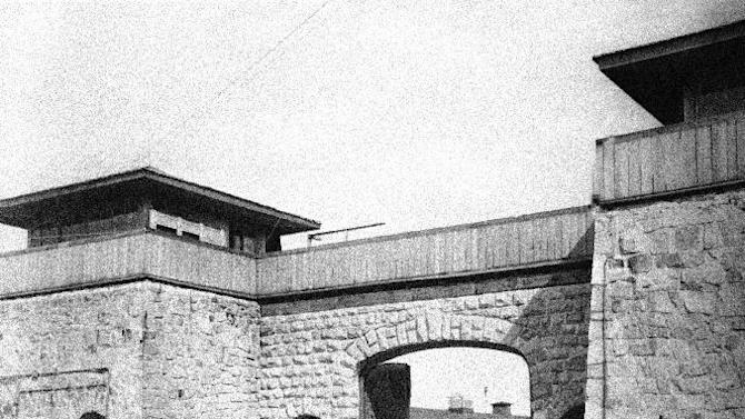 FILE - This July 1945 file photo shows the main gate at Mauthausen concentration camp, near Linz, Austria. An Associated Press investigation found dozens of suspected Nazi war criminals and SS guards collected millions of dollars in Social Security payments after being forced out of the United States. (AP Photo/Lynn Heinzerling, File)