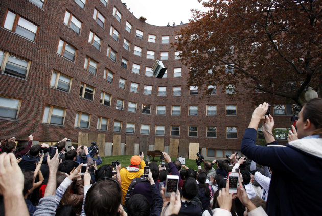 RETRANSMISSION TO CORRECT DAY OF WEEK - A crowd watches as a piano falls from the roof of Baker House dormitory at Massachusetts Institute of Technology in Cambridge, Mass., Thursday, April 26, 2012. The annual event which began in 1972 is staged to celebrate the last day students can drop classes without having them appear on their college transcript. (AP Photo/Michael Dwyer)