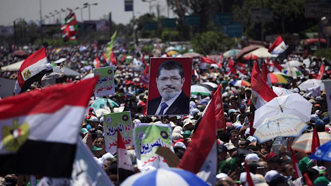 """Supporters of Egypt's president Mohammed Morsi attend a rally in Nasser City in Cairo, Egypt, Friday, June 21, 2013. Tens of thousands of Islamists supporting Egypt's president staged a show of force ahead of massive protests later this month by the opposition, chanting """"Islamic revolution"""" and warning of a new and bloody bout of turmoil. Adding to the combustible mix, the U.S. ambassador in Egypt gets drawn into Egypt's treacherous politics when comments interpreted as critical of the opposition spark outrage, with one activist telling the diplomat to """"shut up and mind your own business."""" (AP Photo/Khalil Hamra)"""