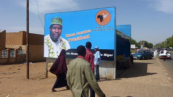 People walk by a campaign poster of Hama Amadou, one of the candidates to the presidential elections in Niger, on January 25, 2011