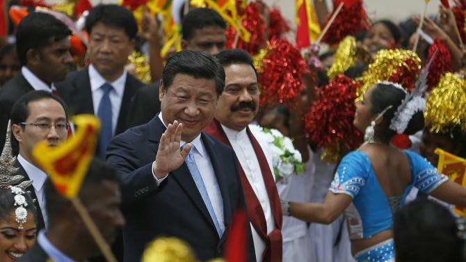 Xi waves next to Rajapaksa during an official welcoming ceremony at Bandaranaike International Airport