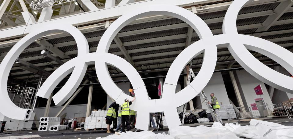 Workers assemble Olympic rings outside the Aquatics venue at the 2012 Summer Olympics in London, Saturday, July 14, 2012. (AP Photo/David J. Phillip)