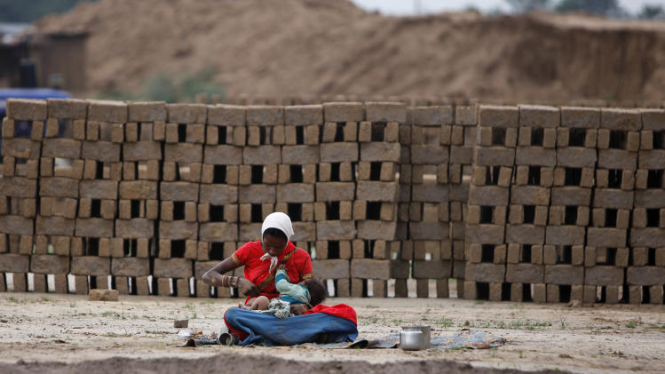 A woman laborer takes a break with her child at a brick factory on the outskirts of Jammu, India, Tuesday, May 1, 2012. May Day is being marked across the world Tuesday. (AP Photo/Channi Anand)